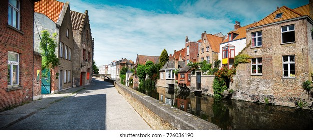 Bruges canal on a sunny day with buildings reflecting on the water