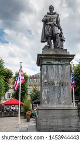 Bruges, Flanders, Belgium -  June 17, 2019: Simon Stevin statue on his own square where people enjoy drinks under cloudscape. Flags and green foliage.