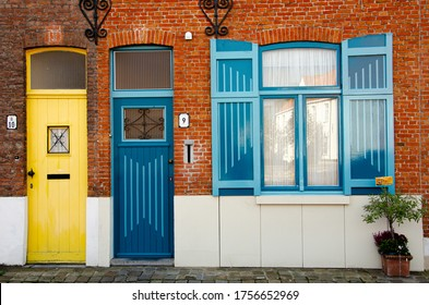 Bruges, West Flanders / Belgium - 10/26/2019 - Beautiful front house on a canal in Bruges, the capital of West Flanders, Belgium. Yellow door next to blue door and blue windows.