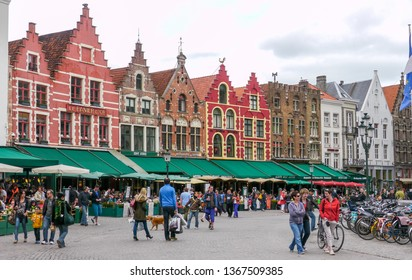Bruges, West Flanders / Belgium - May 4th, 2013: People strolling by Market Square / Colorful facades and green shop awnings