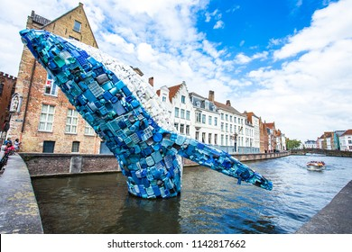BRUGES,BELGIUM-JUNE 16 : Skyscraper or the Bruges Whale rises up from the Bruges canals, the animal is made of waste, collected from the plastic soup that floats on the seas and oceans of the world.