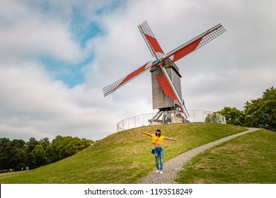 Brugge Belgium, colorful house at the old city of Brugge , young woman free in the city by the old windmill,Bruges, Belgium. Sint Janshuismolen wind mill dating from 1770, still in its original spot