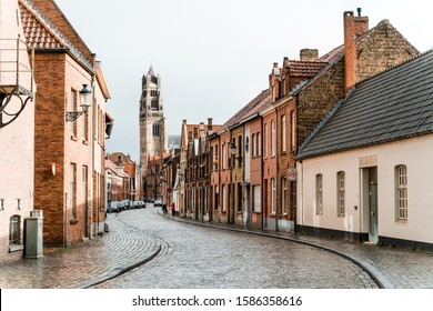 Brugge, Belgium - May 2019: Ancient streets of the old city of Brugge in Belgium. An empty street from a lumber block extending into the distance in rainy weather.
