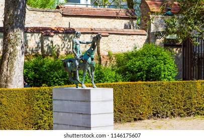 BRUGGE, BELGIUM - MAY 6, 2018: Photo of Sculptural group of horsemen of the Apocalypse in the park Arentshof. Fragment.