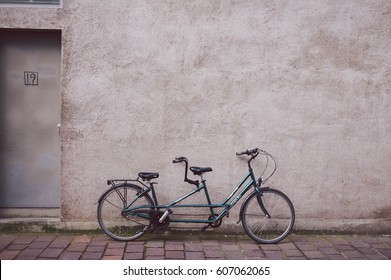 Brugge, Old Town, Belgium - April 21, 2016: Green bicycle against gray wall on the empty street.