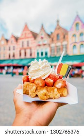 Brugge waffles Belgium, Waffle with cream and strawberry, waffle isolated in hand