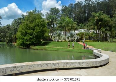 BRUMADINHO, INHOTIM, MINAS GERAIS/BRAZIL - FEBRUARY 2013: Inhotim park, lake and visitors along path on Brumadinho, view from Tunga True Rouge pavillion Minas Gerais/Brazil.