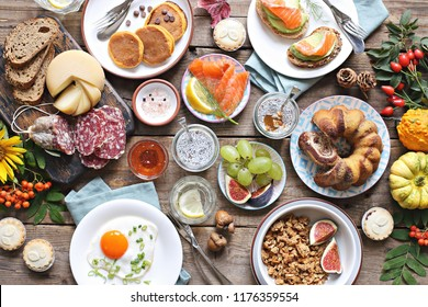 Brunch. Breakfast food table. Festive brunch set, meal variety with fried egg, pancakes, granola, sweets and berries. Overhead view
