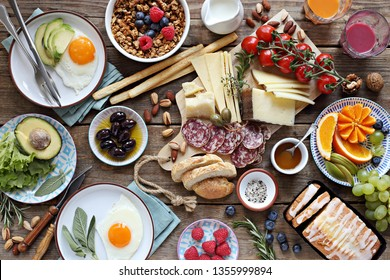 Brunch or breakfast set, meal variety with fried eggs, sausage and cheese variety, granola, smoothie, fruits and berries. Overhead view