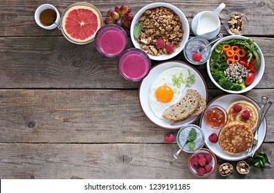 Brunch or breakfast table. Festive brunch set, meal variety with quinoa salad bowl, fried egg, granola, pankes, chia seeds pudding and smoothy  . Overhead view