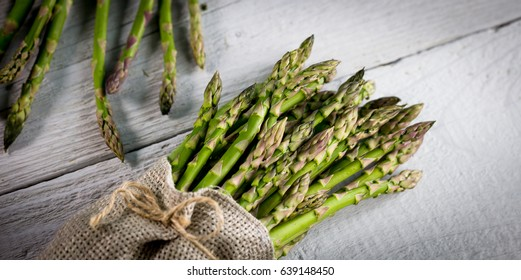 The Brunch of Fresh BIO Green Aspargus  on vintage wooden background. place for text