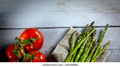 The Brunch of Fresh BIO Green Aspargus and Tomatoes  on vintage wooden background. place for text