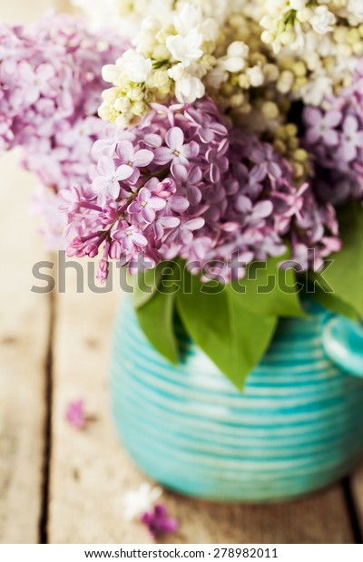 Brunches of white and purple lilac in vase