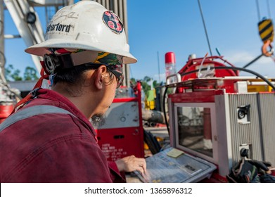 BRUNEI DARUSSALAM - April 2019: Oil and gas worker watching and monitoring pressure control screen and wearing complete safety helmet, glass and coverall