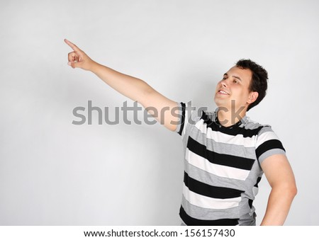 Brunet man in striped T-shirt smiles and points to side on grey background.