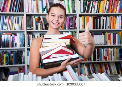 brunete girl chose a lot of books in university library shows thump up