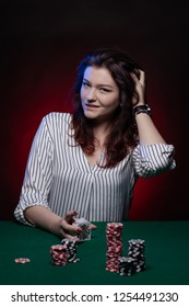 Brunette actress girl plays cards over green cloth posing on a dark background in blue and red light.