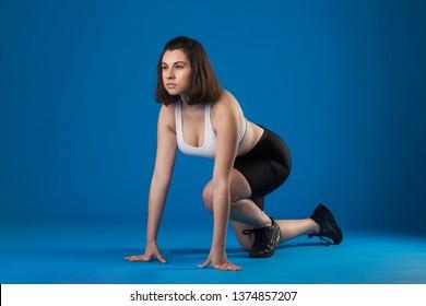 Brunette athlete girl on a blue background. studio photography