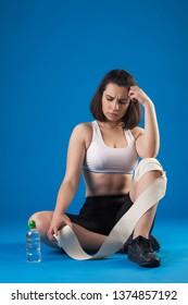 Brunette athlete girl wraps leg with a bandage on a blue background. Sports injury.