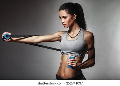 brunette athletic woman exercising with rubber tape