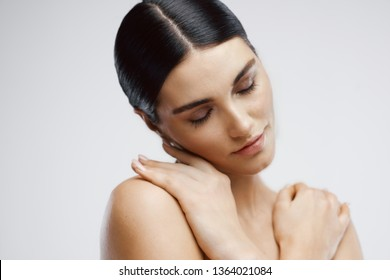 Brunette with bare shoulders cosmetology skin care SPA procedures