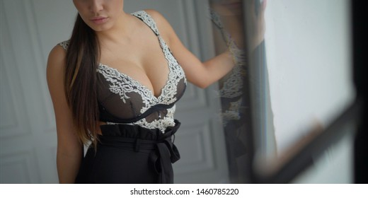 Brunette with a beautiful natural breastsю Seductive decollete concept. Portrait of beautiful brunette. Natural hairstyle, perfect make-up. Black lace cocktail dress. Healthy hair