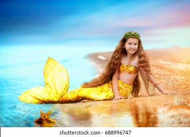 Brunette beautiful Siren Mermaid . Mermaid girl with gold tail put feet in water. Top view. Fun, vacation concept. Text space