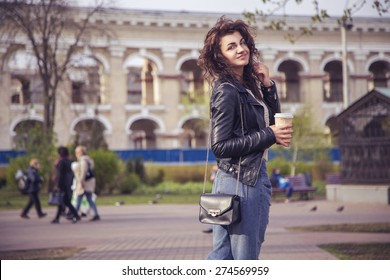 Brunette beautiful stylish caucasian woman in casual outfit on a walk on european city street drinking coffee. copy space