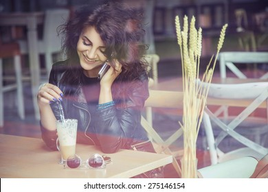 Brunette beautiful stylish caucasian woman in casual outfit on a walk on european city street sitting at the cafe talking on her phone. copy space