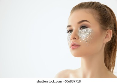 Brunette beautiful woman with crystals on face. Fashion creative make-up with Swarovski. Isolated on white background. Copy space