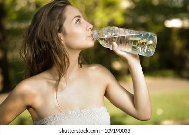 Brunette beauty drinking bottled water on a hot summer day.