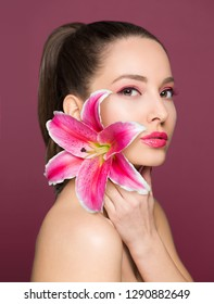 Brunette beauty in light makeup holding colorful lily flower.