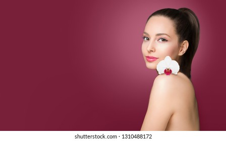Brunette beauty in light makeup holding colorful flower.