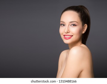 Brunette beauty in light makeup smiling at the camera.