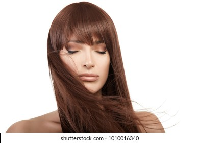 Brunette beauty model girl with healthy straight long hair blowing over her face wearing subtle eye makeup in a closeup beauty portrait with copy space. Haircare concept