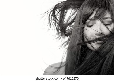 Brunette beauty model girl with healthy straight long hair blowing over her face wearing subtle eye makeup in a monochrome closeup beauty portrait with copy space. Haircare concept