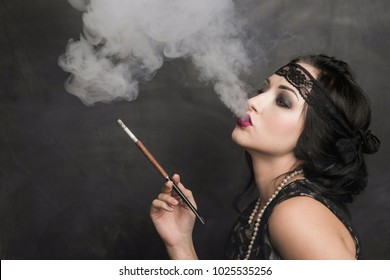 brunette in black dress in the style of decadence holds the mouthpiece and blows smoke