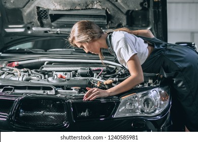 A brunette in a black jumpsuit and a white t-shirt near the open hood. Young female in the garage is smiling at the camera and lowered gaze. car repair concept