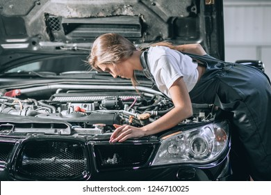 A brunette in a black jumpsuit and a white t-shirt near the open hood of black car. Young female in the garage. car repair concept