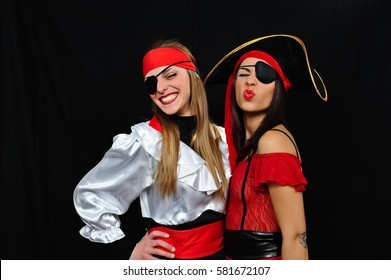 brunette and blonde girl poses wearing pirates carnival costume and hat