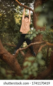 brunette boy hangs on a tree branch in the forest. A park. Outdoor. Summer day. holidays