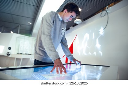Brunette boy interacting with large touch screen in museum stand exhibition