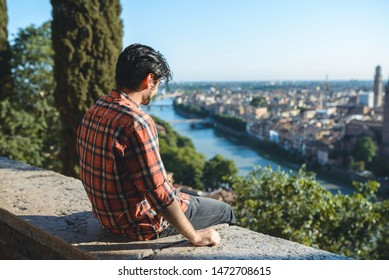 brunette boy sitting on hill with view on river