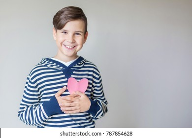 A brunette boy in a striped sweater holds a pink heart of paper in his hand. Beautiful smile. Gray background. Free space. Inside the room. Daylight. The teenager holds the heart at his chest.