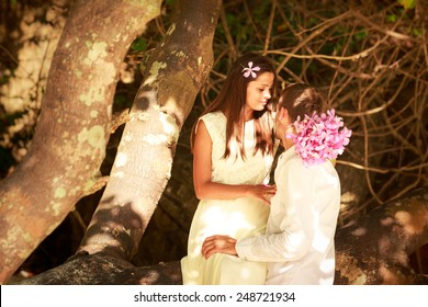 brunette bride in long white wedding dress sitting on the big tree and hold her handsome groom on island beach in Thailand