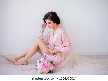 Brunette bride in pink silk robe and long veil sits on the floor holding pink wedding bouquet