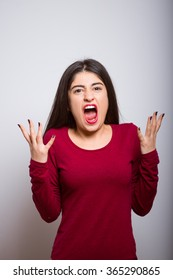 brunette business woman shouting angry, in a red dress, studio isolated portrait emotions