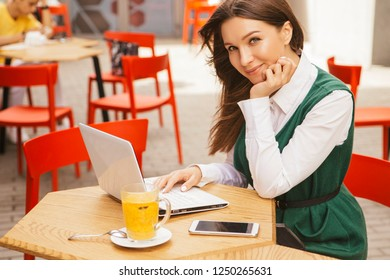 Brunette business woman working as a freelancer from a cafe in summer terrace. She drinks tea and use gadgets as laptop and tablet and phone for her work. Space for text