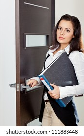 brunette businesswoman holding file and opening the dark brown door