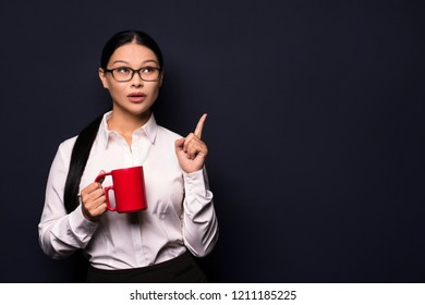 Brunette businesswoman in office clothes posing on camera. Holding red coffee cup.